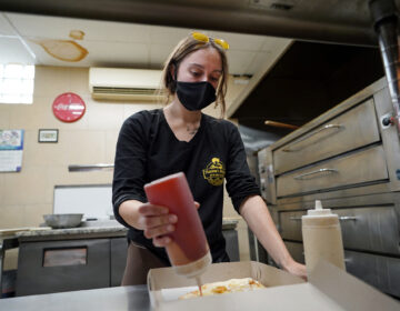Jessica Symes, a senior at Kutztown University, works on a pizza order at Mamma's Delight Pizza Restaurant in Kutztown, Pennsylvania. (Matt Smith for Keystone Crossroads)