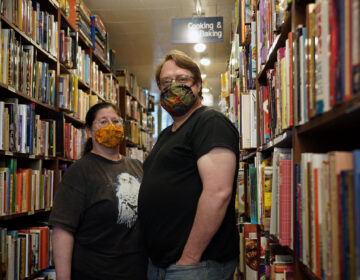 Co-owners Rebecca Laincz, left, and Matthew Williams, right, stand in an aisle at Firefly Bookstore in Kutztown, Pennsylvania. (Matt Smith for Keystone Crossroads)