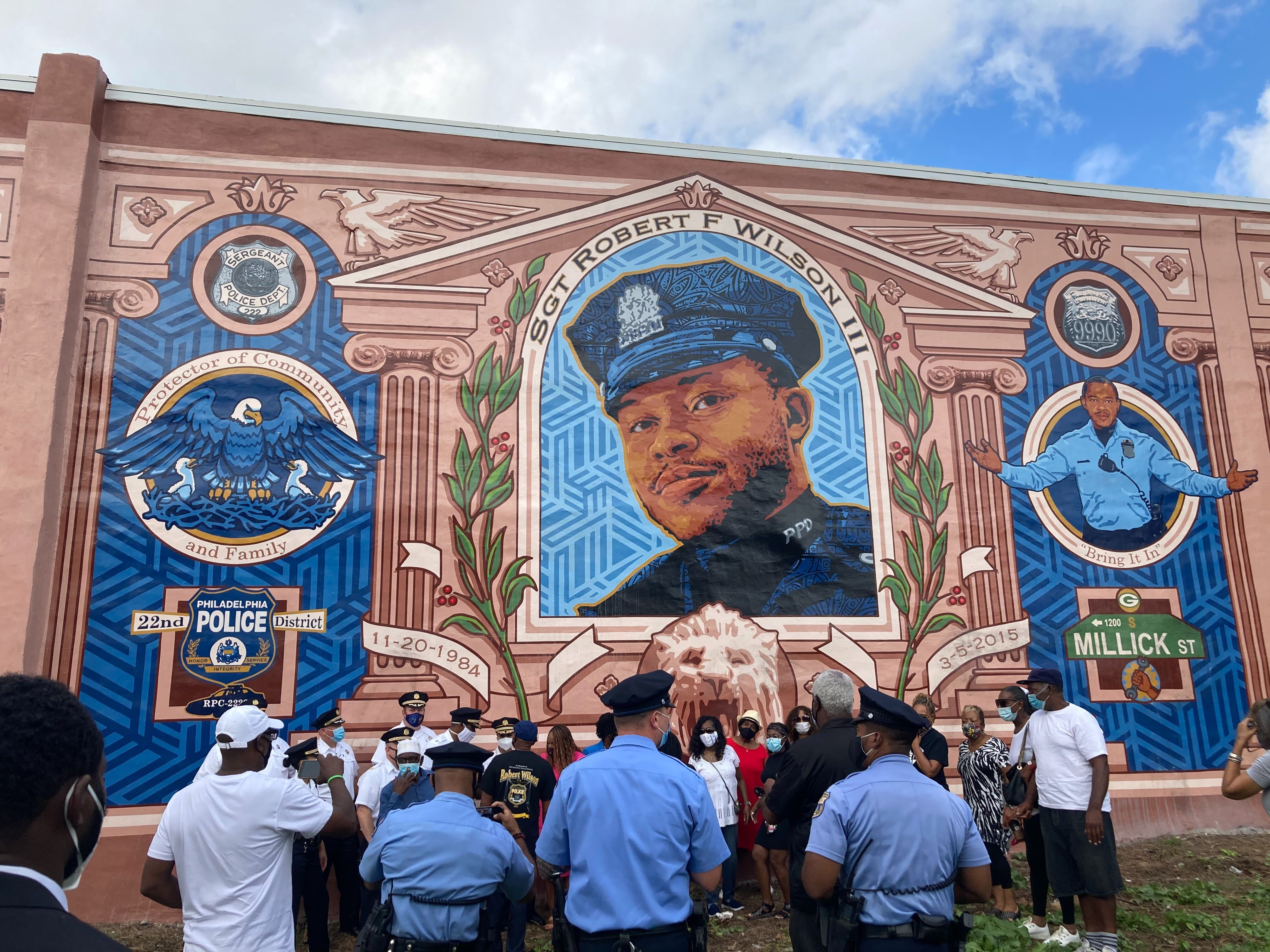 City officials, police officers from the 18th district, and neighborhood residents pose in front of the Sgt. Robert Wilson III mural
