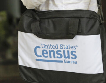 A U.S. Census Bureau worker carries a briefcase while knocking on the door of a home in August in Winter Park, Fla. (John Raoux/AP)