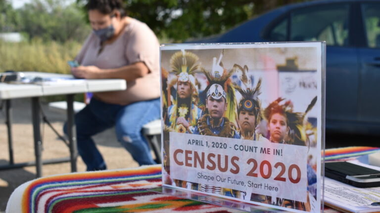 A sign promoting participation in the 2020 census is displayed as Selena Rides Horse enters information into a phone for a member of the Crow Indian Tribe in Lodge Grass, Mont. in August. (Matthew Brown/AP Photo)