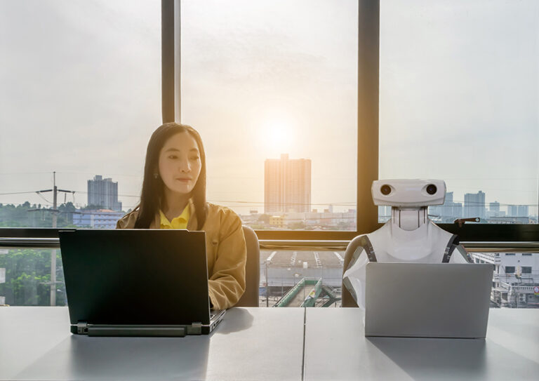 A young woman doing work on a computer, sitting next to a robot working on a computer