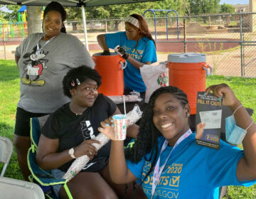 This summer, Nyzia Easterling, left; and teen census workers, from left to right; Eternity Easterling, 14; Janiayah Williams, 16; and Shayla Ingram, 16; pose for a picture while manning a table in a Camden park to promote census awareness. (Courtesy of Saving Grace Ministries)