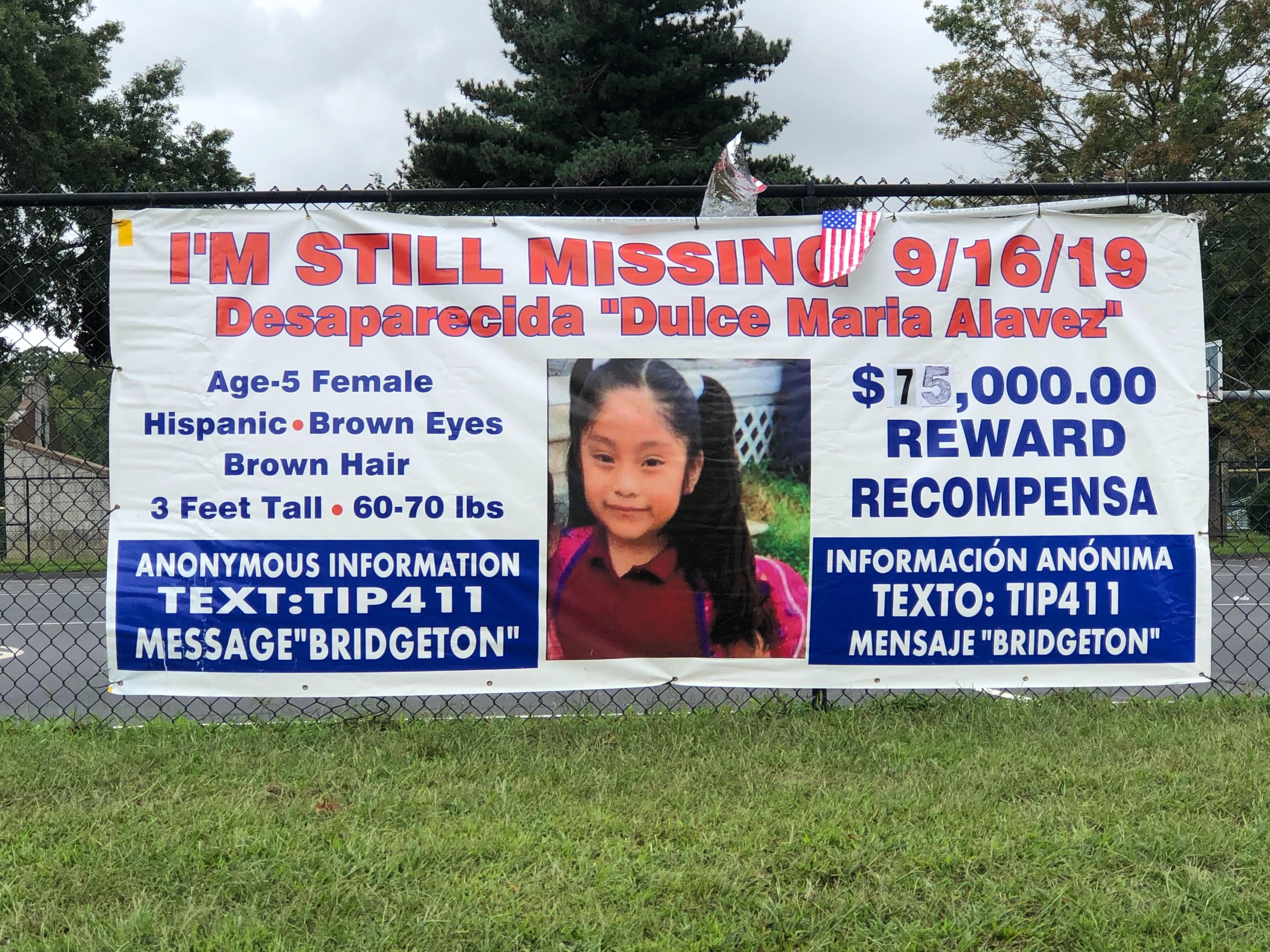 A banner with information on the reward and where to send tips via text in Bridgeton City Park hangs on a fence
