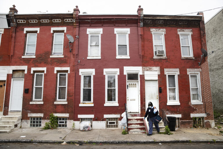 United States Postal Service carrier Henrietta Dixon walks her route to deliver mail in Philadelphia, Wednesday, May 6, 2020. (AP Photo/Matt Rourke)