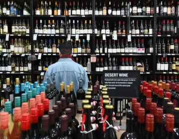A patron stands in front of a shelf full of wine bottles at a liquor story in the Brooklyn borough of New York City on March 20. (Angela Weiss/AFP via Getty Images)