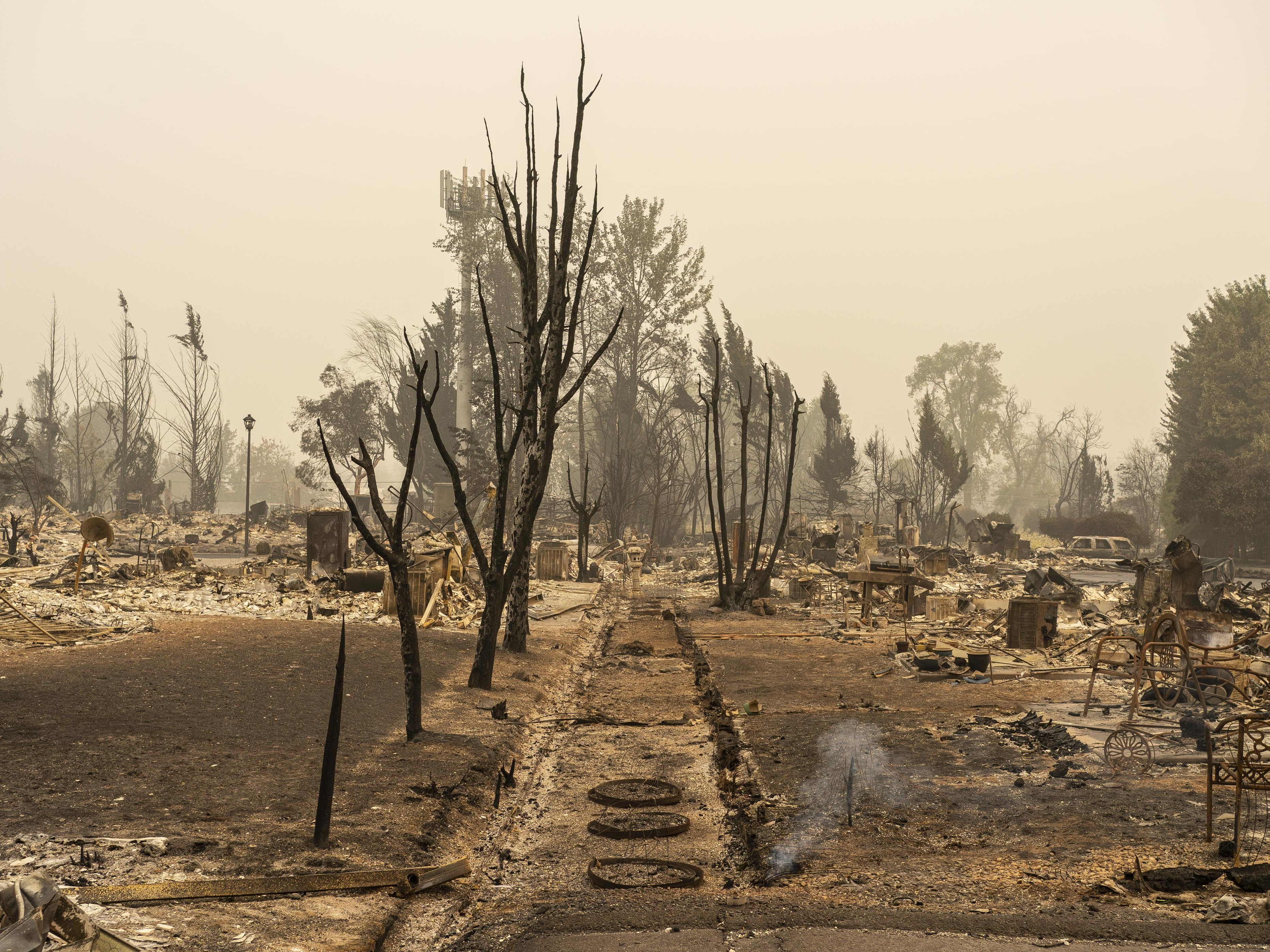 Smoke rises from the ground Sunday in a neighborhood destroyed by wildfire in Talent, Ore.