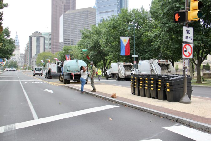 City workers with garbage trucks and bins for possessions wait on the Ben Franklin Parkway