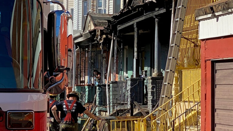 A Philadelphia firefighter stands in front of a charred rowhouse after a deadly blaze in Kensington. (NBC10)