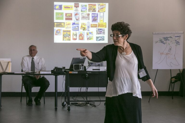 In this Feb. 11, 2015, photo, veteran LAPD officers Don Wynne, left, and Ann Bozzi instruct dozens of unidentified Los Angeles Police Department officers learn to recognize unconscious prejudices and how they can impact behaviors on the street at a class at the Museum of Tolerance in Los Angeles. The department, which expects to send more than 5,000 officers to the museum's course in the next several years, is working to weave implicit bias lessons into existing training. (AP Photo/Damian Dovarganes)