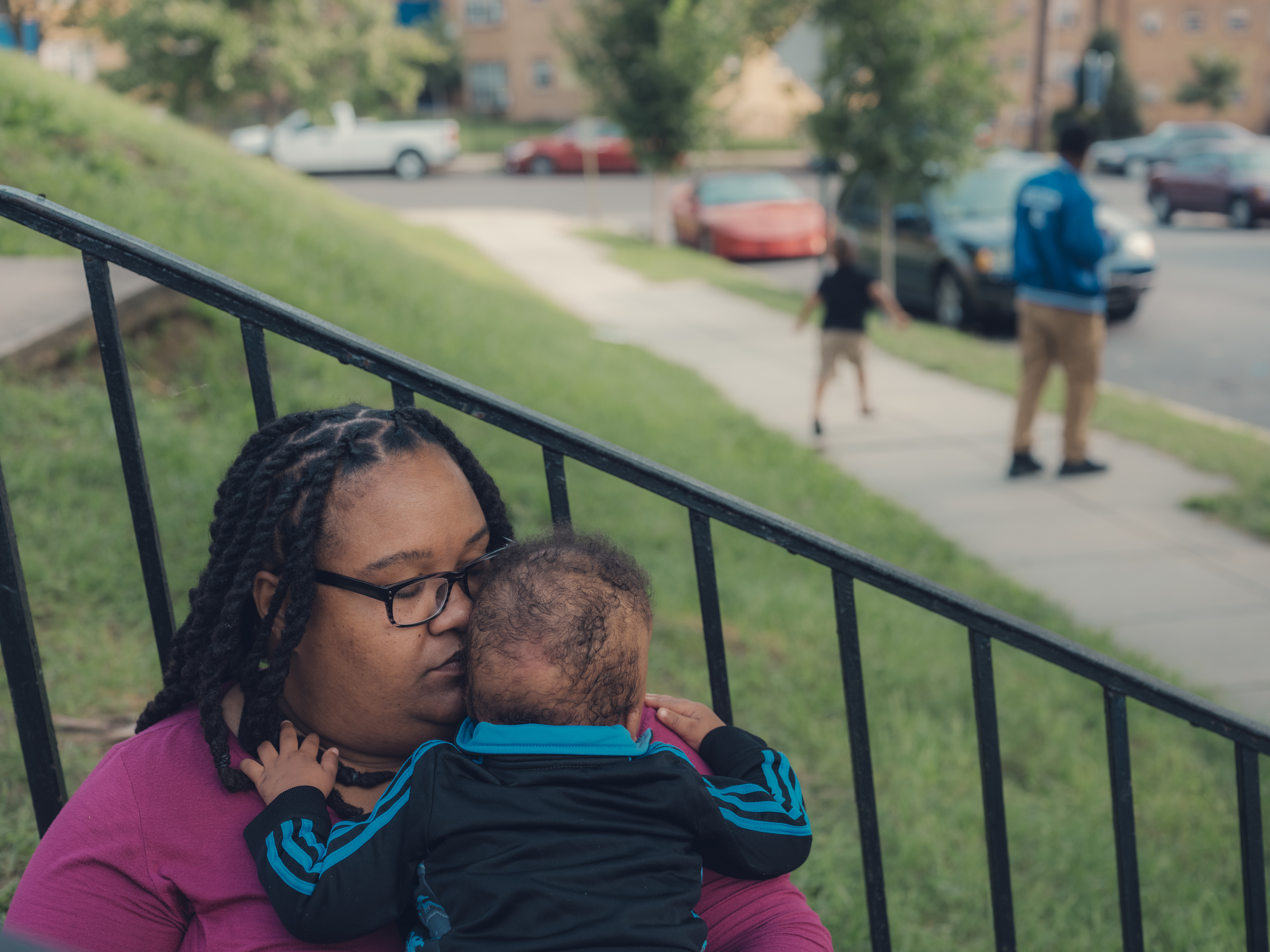Patricia Stamper holds her younger son, 1, at their home