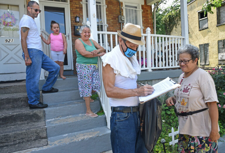 In East Camden, Nelson Berrios signs the petition for nonpartisan elections for Mary Cortes, right on Aug. 22.  (April Saul for WHYY)