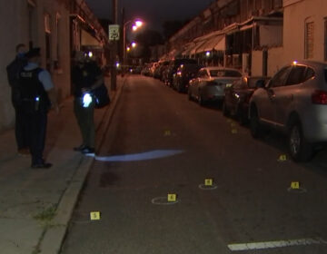 Philadelphia Police Department investigators stand on a sidewalk as bullet casings and evidence markers lay on the ground after a shooting