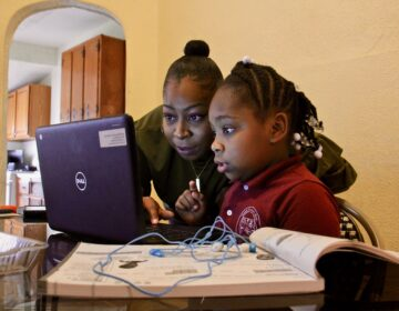 Yolanda Biggers helps her daughter, Zyiah Satterwhite, 7, find her assignment.