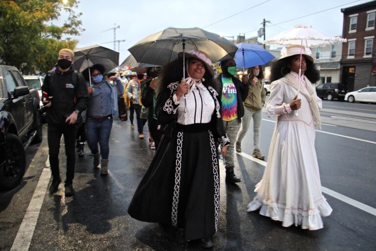 Jeannine Cook (right) owner of Harriett's Bookshop in Fishtown, and her sister Jasmaine Cook, lead a procession on East Girard Avenue