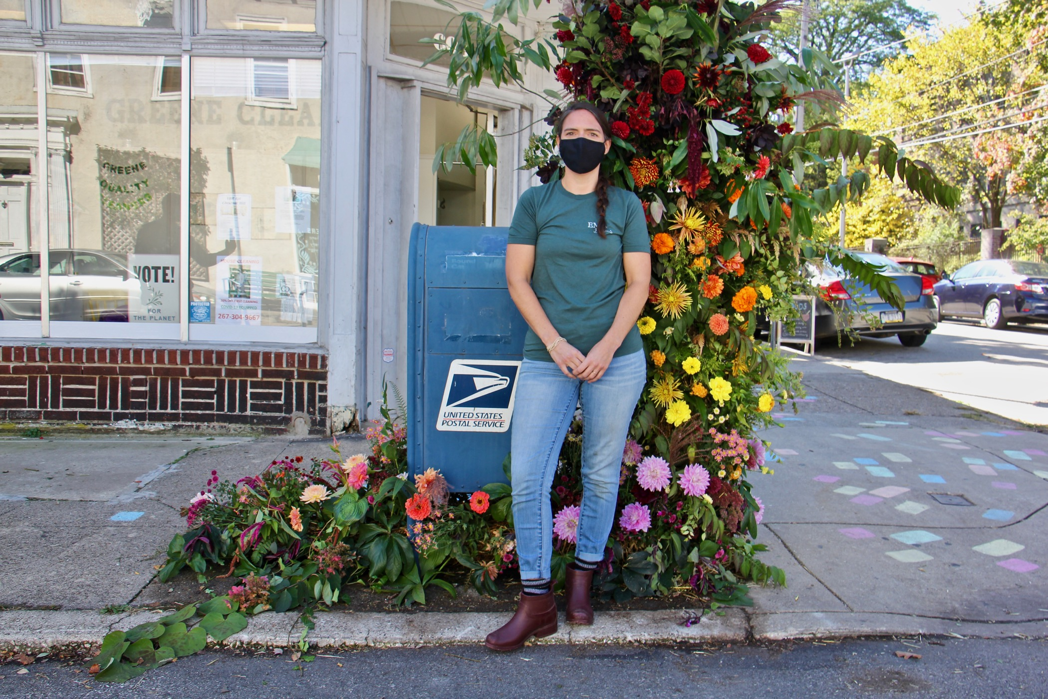 Florist Kate Carpenter stands my her floral arrangement by a mailbox.