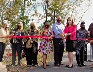 Willingboro Mayor Tiffani Worthy (center) joins local and county officials to cut the ribbon on the township's first county park. (Emma Lee/WHYY)