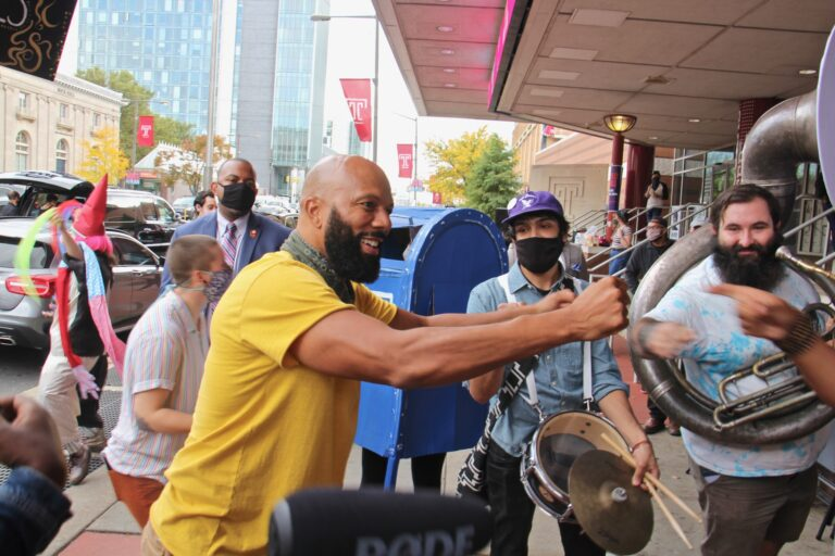 Common, the rapper also known as Lonnie Rashid Lynn, bumps fists with members of the Snack Time Band outside the Liacouras Center after an impromptu jam session. (Emma Lee/WHYY)