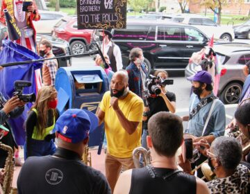 Common jams with the Snacktime Band outside the Liacouras Center, a surprise addition to the Cirque d'Vote entertainment for voters waiting in line there. (Emma Lee/WHYY)