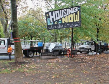 Workers put up fences around the Von Colln Field as the homeless encampment there is disassembled. (Emma Lee/WHYY)