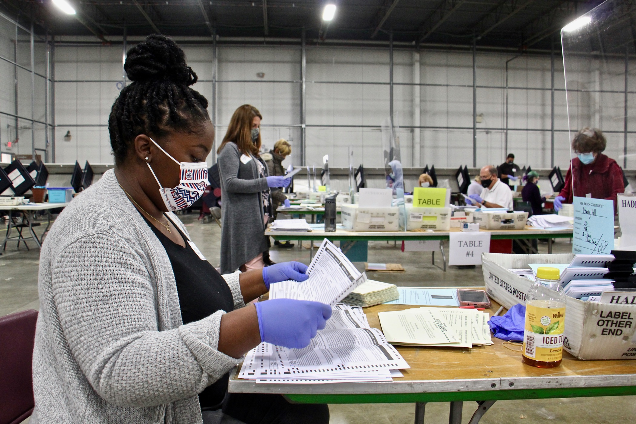 Rickia Bagwell of Lindenwold opens and inspects mail ballots