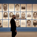 District Attorney Larry Krasner views 'Redaction,' a mural of portraits by Titus Kaphar and Reginald Dwayne Betts in the gallery of the African American Museum of Philadelphia.(Peter Crimmins/WHYY)