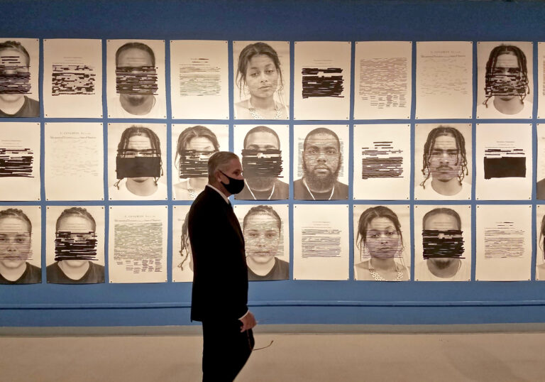 District Attorney Larry Krasner views 'Redaction,' a mural of portraits by Titus Kaphar and Reginald Dwayne Betts in the gallery of the African American Museum of Philadelphia