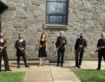 Musicians standing outside a stone building holding their instruments and wearing masks