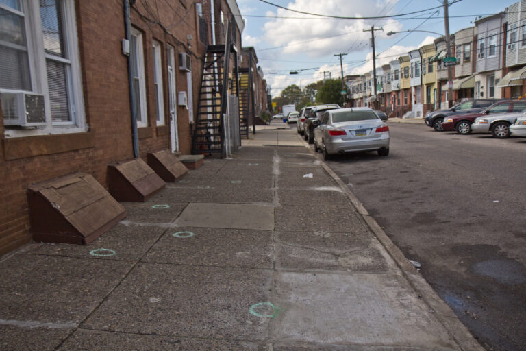 Chalk circles drawn on the sidewalk mark where shell casings landed at 22nd and Jackson Streets in South Philadelphia. (Kimberly Paynter/WHYY)