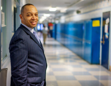 Richard Gordon, principal of Paul Robeson High School, in hallway with lockers