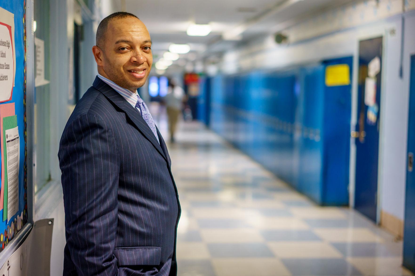 Richard Gordon, principal of Paul Robeson High School, in hallway with lockers