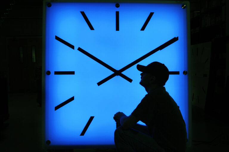 In this Oct. 30, 2008, file photo, Electric Time Company employee Dan Lamoore adjusts the color on a 67-inch square LED color-changing clock at the plant in Medfield, Mass. (AP Photo/Elise Amendola)