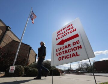 In this Feb. 26, 2020 file photo, using both the English and Spanish language, a sign points potential voters to an official polling location during early voting in Dallas. (LM Otero/AP Photo)