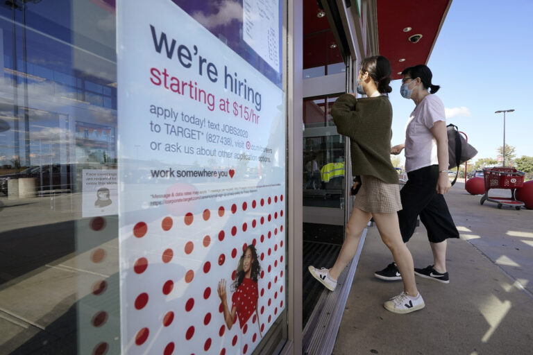 Passers-by walk past a hiring sign as they enter a Target retail store location, Wednesday, Sept. 30, 2020, in Westwood, Mass. (AP Photo/Steven Senne)