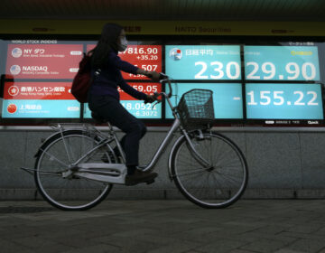 A woman rides a bicycle  past an electronic stock board showing Japan's Nikkei 225 index at a securities firm in Tokyo Friday, Oct. 2, 2020. (AP Photo/Eugene Hoshiko)