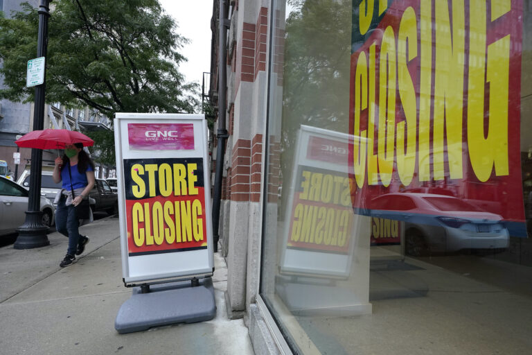 In this Sept. 2, 2020, file photo, a passerby walks past a business storefront with store closing signs in Boston. (AP Photo/Steven Senne)