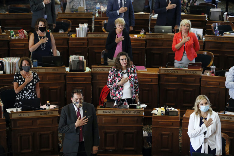 In this Wednesday, June 3, 2020 file photo, State Representatives stand at their desks during the Pledge of Allegiance in the Iowa House chambers, at the Statehouse in Des Moines, Iowa. (AP Photo/Charlie Neibergall)