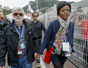 Mellody Hobson, right, walks with film director George Lucas after the qualifying session at the Monaco racetrack in Monaco, Saturday, May 25, 2013. (AP Photo/Claude Paris)