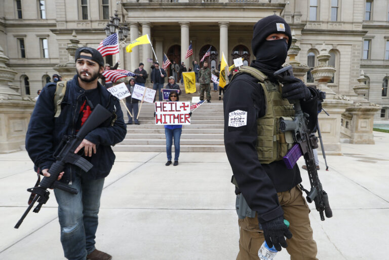 In this April 15, 2020 file photo, protesters carry rifles near the steps of the Michigan State Capitol building in Lansing, Mich. (AP Photo/Paul Sancya)
