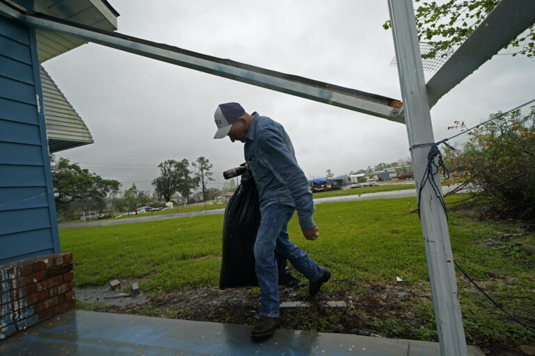 Jim Fontenot carries possessions into his brother's home, to which his family temporarily relocated to ride out Hurricane Delta which is expected to make landfall later in the day, in Lake Charles, La., Friday, Oct. 9, 2020. (AP Photo/Gerald Herbert)