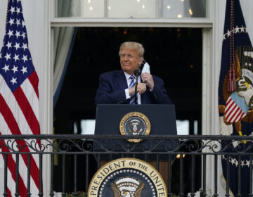President Donald Trump removes his face mask to speak from the Blue Room Balcony of the White House to a crowd of supporters, Saturday, Oct. 10, 2020, in Washington. (AP Photo/Alex Brandon)