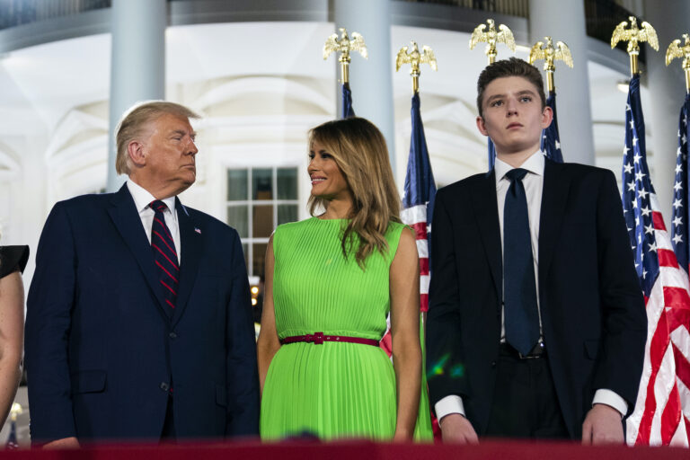 In this Aug. 27, 2020 file photo, Barron Trump right, stands with President Donald Trump and first lady Melania Trump on the South Lawn of the White House on the fourth day of the Republican National Convention in Washington. (AP Photo/Evan Vucci)