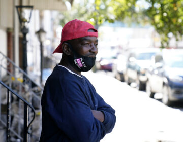 Black man standing on West Philadelphia face mask donning a face mask
