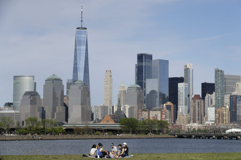 In this Saturday, May 2, 2020 file photo, people sit in view of Lower Manhattan at Liberty State Park in Jersey City, N.J. (AP Photo/Seth Wenig)