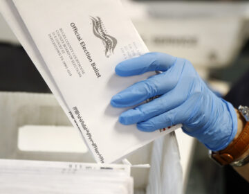 In this May 27, 2020 file photo, a worker processes mail-in ballots at the Bucks County Board of Elections office prior to the primary election in Doylestown, Pa. (AP Photo/Matt Slocum)