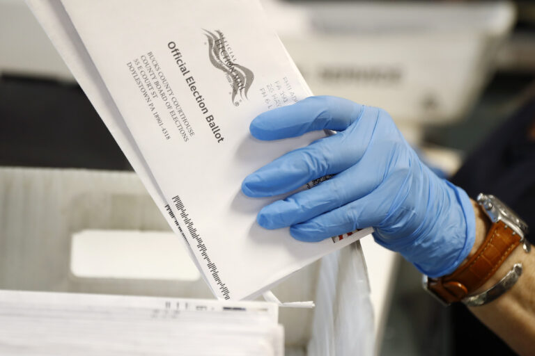 A worker processes mail-in ballots
