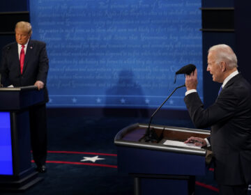Democratic presidential candidate former Vice President Joe Biden holds up a mask as President Donald Trump takes notes during the second and final presidential debate Thursday, Oct. 22, 2020, at Belmont University in Nashville, Tenn. (AP Photo/Morry Gash, Pool)