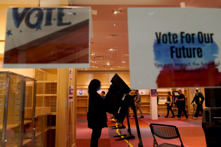 A woman casts her ballot on the first day of early voting in a recently-shuttered store at Oak Park Mall Saturday, Oct. 17, 2020, in Overland Park, Kan. (AP Photo/Charlie Riedel)