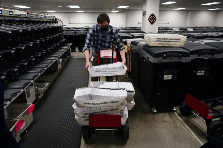 Michael Imms, with Chester County Voter Services, gathers mail-in ballots after being sorted for the 2020 General Election in the United States, Friday, Oct. 23, 2020, in West Chester, Pa. (AP Photo/Matt Slocum)