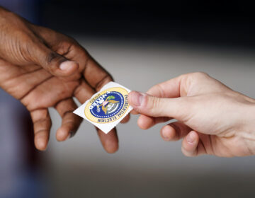A man is handed a sticker from a volunteer after dropping off his ballot for the 2020 General Election in the United States outside the Chester County Government Services Center, Friday, Oct. 23, 2020, in West Chester, Pa. (AP Photo/Matt Slocum)